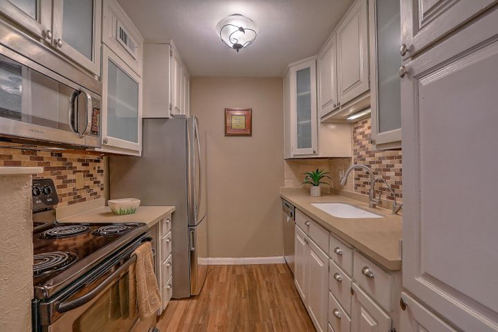 Come home to this gorgeous ground floor unit and enjoy an upbeat, carefree lifestyle in the heart of the highly desirable Uptown area.  Winrock Villas Condos are located in a fully maintained lush setting of manicured lawns, shrubs, flowers and trees,  with 3 outdoor pools/indoor pool, hot tub, sauna, exercise room, Clubhouse, laundry facilities, and designated covered parking w/small personal storage area.  Pride of ownership is reflected throughout this tastefully designed 2 bedroom, 2 bath condo with beautiful wood grained tile floors, stylish kitchen back splash, upgraded cabinets, fresh paint, updated baths with tasteful tile & fixtures plus refrigerated air.  HOA fees cover all utilities, property taxes, roof/exterior and common area maintainence. Near shopping, dining/entertainment.