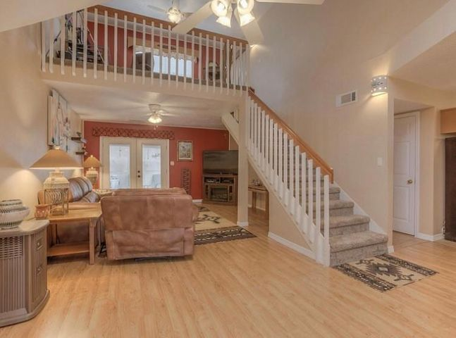 Come home to this Cheerful, Light & Bright open floor plan with Cathedral Ceilings!    Main floor includes LR/ Dining Area, Kitchen and Bedroom + Full Bath - could be a 2nd master.  French doors from LR lead to extended covered patio & walled yard area w/ built-up planters.  New plush carpet on stairway leads to upper level which include the newly carpeted Loft & MBR w/Full Bath,  and access to your private deck w/mountain and city light views.   Extensive recent updates include  new shingled pitched roof,  paint,  beautiful tile and wood-look laminate flooring,  plush upstairs carpet, skylight, refinished cabinets, and ceiling fan.   Front & back landscaping w/auto timers & flower bed.    MOVE IN READY!   Wonderful location near groceries, restaurants and short drive to I-40 on ramp. WOW!