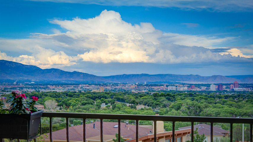 The ultimate luxury ''Crash Pad'' for executives or movie industry Pros! Sophisticated 2725 sqft property perched high on the Bluff overlooking the Rio Grande valley, clear across to the mountains!  Built in 2005, with an amazing floorplan for any lifestyle and for those who love to entertain -PEFRECTION! Rich warm tones, modern lighting, travertine floors, spacious kitchen w/bar seating, center prep-island, granite countertops open to the greatroom with a Kiva fireplace and those VIEWS. Formal or informal dining, Incredible main level owner's suite appointed nicely w/a steam shower, jetted tub, 2 vanities & walk-in closet. The walkout lower level ROCKS a gameroom, bedroom ensuite, theater or potential 3rd bdrm & kitchenette. Both levels have expansive outdoor living spaces ABQ DREAM HOME!