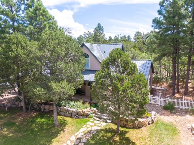 Escape to this private custom mountain retreat nestled among the tall Ponderosa Pines. Lush lawn,  blooming flowers and quaint stone path welcome you into this light and bright Tijeras home. Totally turn-key with gorgeous grey stained cabinetry, coordinating granite tops and stainless appliances.  Large picture windows, freshly painted interior, updated laminated floors plus tile (carpet free!), and recent metal roof. Downstairs master boasts charming window seat, updated en-suite with jetted tub and separate shower. Cozy pellet stove, in-floor radiant heat and well insulated walls will keep you nice and warm in the winter.  Tranquillo Pines Community water! Quaint front porch, private back patio with pond and flagstone; neighborhood park, and trails nearby and 20 minutes to ABQ!