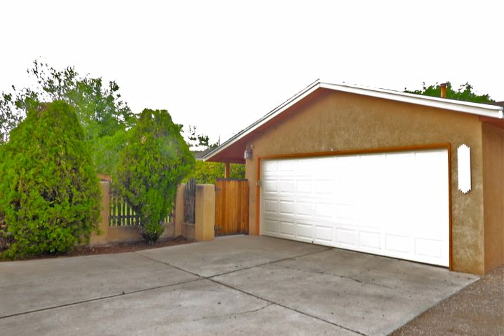 Welcome to this charming, move-in ready home with 3 bedrooms, 2 full baths & hard to find, attached 2-car garage in West Old Town just minutes to Old Town Plaza & the river trails. Updates include a new garage door & opener, newer roof, thermal windows, sliding patio door, REF AC, plus NO carpet! The open floor plan features a huge 17x18-ft great room that opens to the dining area & kitchen with newer appliances & new disposal. The home sits on a 0.19 ac. lot that's nicely landscaped with grass, shade trees & quaint path leading from the rear to front yards. There is plenty of room on the eastside of the house to park extra vehicles including a RV! Located on Bicycle Blvd for an easy commute to work in the DT & UNM areas with easy access to restaurants, shopping & every imaginable amenity!