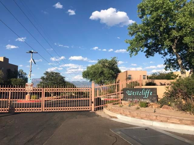 Spectacular Views of the Mountains, Valley and City! In the morning you can see the Hot Air Balloons on parade without lifting you head from your pillow. In the evening, the city lights will twinkle and shine. Well maintained split level town home with floor to ceiling windows the entire width and height of the East facing walls. Gated community, club house, pool and access to walking trails along the Bosque.  This unit sits on top row of complex adding to your privacy. Numerous recent updates include: 2019 - Brand New slider in Master and carpet in all bedrooms and stairway, 2018 - Refrigerator , Stove Top, and Hot Water Heater, 2016 - Refrigerated Air/Heating system, 2012 - Evaporative cooler. Convenient to I-40, Shopping, numerous restaurants, gas stations and amenities. Come See Today!