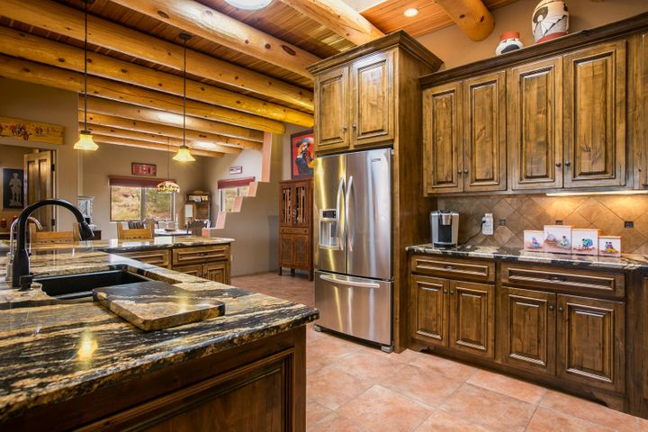 This single-level Southwest style home, located on a .91 acre view lot in Anasazi Meadows, was built with the incredible views of the Sandia Mountains in mind. Its features include raised, beamed and latilla ceilings, tile floors throughout, lighted nichos and custom wood burning kiva fireplaces in the great room & master. The kitchen features custom cabinets w/ pull out shelves, level 5 granite counters, stainless appliances, pantry and breakfast bar. Enjoy the views from the spacious master bedroom which features an exercise/sitting area opening to the covered patio. The en-suite bath features a massive closet, jacuzzi tub, large shower and water closet. Outdoor living spaces offer many opportunities for entertaining or relaxing! Please click ''more'' for additional features & informatio