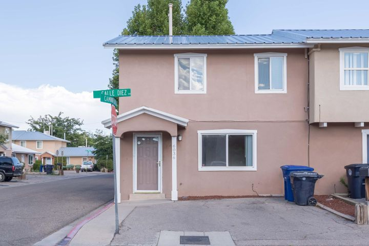 Enjoy the North Valley in this wonderful townhome!  Across the street from the lush green of the park sits this 2 bedroom 2 bath home.  The main floor has beautiful New Mexican style tile throughout.  In the kitchen is a bar for seating and a breakfast nook with access to the backyard.  Upstairs are beautiful wood floors in the bedrooms!  No carpet!  Close to great restaurants, paths, and all the wonderful things about living in the North Valley!  Come see it before it's gone!