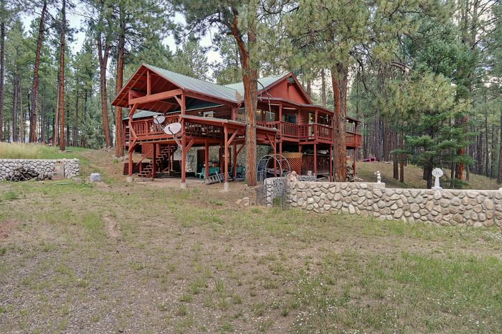 Wow!  What a fabulous new price! Location, location, location!  Two full ponderosa pine acres of Jemez Mountain paradise. Strong and solid cabin or full-time home. Beautiful sun room! Covered decks and huge screened-in porch for those fabulous fall barbecues. Inside you will find a gorgeous two story rock fireplace for those snowy winter nights.  Kitchen is well appointed and has wonderful counterspace, lots of cabinets, and three pantires!  There are bedrooms and baths for everyone. Enough garage space for your truck, car, and toys!  Make it yours!