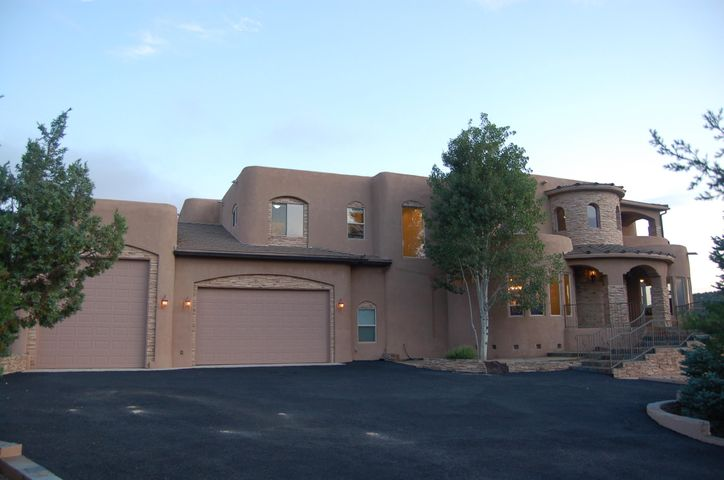 2 large balconies overlooking the 20th hole of the Paa-ko Golf Course, views of the Sandia mountains and the valley below, 3 stories of elegance, a putting green, walnut floors, granite kitchen countertops, Viking appliances,  movie theater room, game room, 4 bedrooms with private bathrooms, built in SS Viking gas BBQ, huge RV garage, exercise room or 5th BR, loft area looking down onto the middle floor, well designed architecture, beautiful round window sitting area great for reading with magnificent views inside the massive master bedroom and so many other wonderful things about this home that make it fantastic! View the photos then set an appointment to come view it. Considering buying? TEST DRIVE THIS HOUSE before you buy as you can rent the home for 30+ days before making an offer!