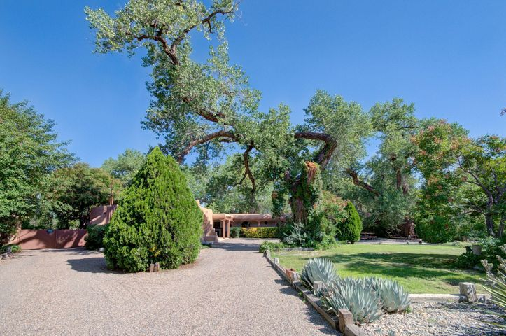 BEAUTIFUL HACIENDA STYLE HOME!!  A True LOS RANCHOS BEAUTY!  BEAUTIFUL ''Portal''  THREE porches to WELCOME you! ALL on 1.18 of an ACRE. BEAUTIFULLY landscaped TREES, SHRUBS, flower beds, & a HUGE GARDENarea! GOT B&B? NEED an in Law Suite? TWO GENEROUS master suites! W/ private Kiva/ Horno Style fireplaces. Vigas, Wood Beamed ceilings & CUSTOM DOORS. A CUSTOM ADOBE/Terrone HOME. THREE Car Ports & Oversized garage /Office. An RV PAD w/ ALL the hookups. HORSE Stalls, Tack Room. Nichos, CUSTOM Brickfloors, lighting, & shutters. SO MUCH MORE to lis!. Irrigation/well too! GENEROUS 3rd & 4th GUEST rooms! CUSTOM tile. BEAUTIFULcustom claw foot tub! SPLIT floor plan. INVITING. BRING THE ENTIRE FAMILY.  Custom Stone Fireplace w/ Banco in Family Room AND a CUSTOM Bar for yourleisure.