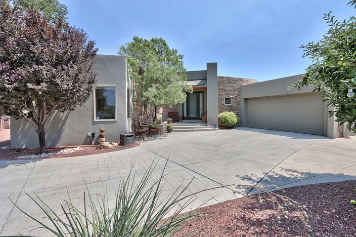 Elegant urban contemporary home.  Enter though gated driveway onto private lot at the end of cul de sac. Stunning single level open great room concept.  Lovely wood floors, contemporary finishes accent the high end features of the updated improved kitchen and living areas. Separated master suites with private access to pool and patio. Flexible floor plan allows for second master suite,  guest room, office and bonus studio or exercise area. Resort at home pool and patio  entertainment off bedrooms and great room. Wood floors, Diamond plaster finishes, custom cabinets, stone and tile throughout the design. Close in North Valley location affords easy commute to downtown, UNM, old town, hospital complexes, Nature Center.  Walk and biking trails everywhere! Low maintenance landscape.