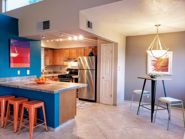 Hillside luxury & easy living in Pinon Creek, nestled against the ABQ Foothills & convenient to Sandia Labs/Kirtland, Trails + Open Space, Quick Freeway Access, 5-10 Min to Uptown, 15min to Nob Hill/UNM!  This contemporary design features a BIG great room w/soaring ceilings, clerestory windows, 20in tile floors,  wood FP & balcony w/colorful sunset & Tijeras Canyon views. Back inside, Kitchen is open concept w/SS appliances, island w/seating, pantry & space to entertain. Spacious master has its own covered patio. A generous guest room has newly upgraded floors & adjacent to full size laundry room (W/D incl!). Both bathrooms are updated, incl oversized soaking tub/shower. Lots of outdoor living space! NEW Stucco! NEW H2O Heater! Upgraded Floors, Fixtures, Furnace + AFFORDABLE price too!