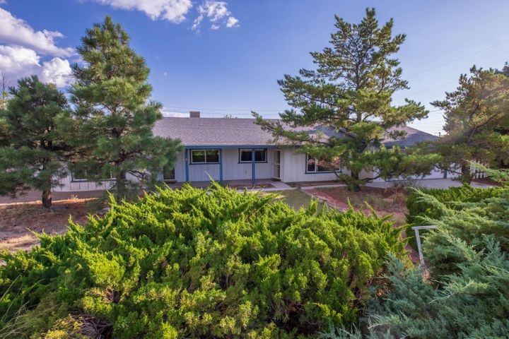 Come see this Ranch style home in the foothills of the Sandias! This home is located on a large corner lot with natural low maintenance landscaping. Convenient access to I-40 and Tramway! With FOUR sliding doors to access the backyard your dream of indoor/outdoor living can become a reality. Some of the many additional highlights of this home include TWO fireplaces, formal dining room, built in sauna, two car garage, and backyard access with no HOA. Call your broker to schedule a showing today!