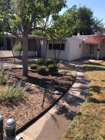Great UNM location,  Two bedroom pueblo style home with converted garage and professional install carport on concrete pad. Fully landscaped front yard with sprinkler system, backyard is walled and fenced for privacy. enclosed back patio. Hardwood floors,  Great home in a great location.