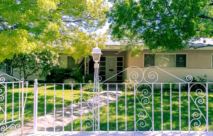 Wonderfully classic one-level home on a beautifully landscaped corner lot close to Hidden Park! Oversized rooms include living room with fireplace, formal dining room with built-in buffet, family room with fireplace and kitchen with breakfast nook. Three huge bedrooms; master suite has walk-in closet, vanity and full bath. Both baths include vintage, original tile. Hardwood floors, crown moldings, French doors, plentiful storage and more. East-facing patio shaded by wisteria. Detached 2-car garage with storage room/workshop. Hot water baseboard heat. Tankless on-demand water heater. Roof new in 2018. Close to UNM and Nob Hill. Note: this home is being offered without floor coverings in hallway and bedrooms.
