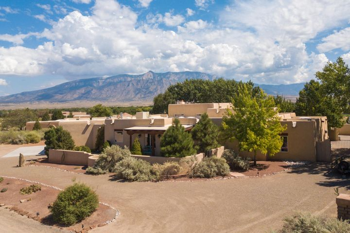 This exceptional one story custom home sits on .5 acre with majestic mountain and city views! Stunning private backyard w/ outdoor kitchen and fire pit- ideal setting for entertaining. This home boasts large bedrooms, Diamond polish plaster walls, a two-way wood burning fireplace, tongue and groove ceiling, a chef's dream kitchen complete with over-sized commercial grade WOLF gas stove including 2 large ovens, Sub Zero fridge,butcher block island  & stunning poured concrete countertops- also in the bathrooms. Slate Floors. Radiant heat. large Master bedrm has separate his/hers walk-in closets. Over-sized 3 car garage w/ multiple work benches, brand new TPO roof. Plenty of room for RV & toys.All in quiet location overlooking Corrales & Bosque plus so much more!