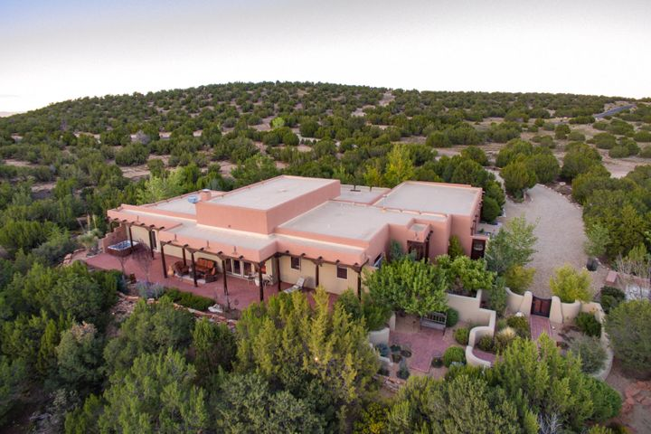 Open Sat 9/21, 1-4pm. Take a YEAR-ROUND VACATION by living in this fantastic San Pedro Creek Southwestern Casa situated on a gorgeous 10 acre setting with panoramic views of the Sandia Mountains. Well-designed pueblo style home with raised beamed ceilings, plastered walls & lovely tiled floors. Owner's suite with separate His and Her bathrooms & large closet. Super kitchen with plenty of cabinetry,  large island & walk-in pantry. 3rd garage bay is converted to studio space. Enjoy amazing sunsets from the 3 outdoor living areas. Bocce court, spa with views, water features, gardens & labyrinth for meditation.  Horses are welcome with nature trails nearby. New roof in 2016, new stucco in 2016, updated septic in 2018. 30 minutes to ABQ. 45 minutes to Santa Fe. Adjacent 10 acres also available.