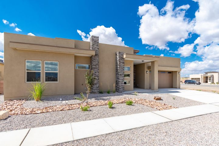 Contemporary, single story, green built beauty by Rhett Ashley Homes located in the Petroglyph Estates. Amazing open floorplan with 2,394sf, 3 bedrooms and 2 bathrooms. Beautiful entryway lined with Clerestory windows. Spacious living area with raised ceilings and a gas fireplace. Stunning kitchen with upgraded cabinetry, quartz countertops, backsplash, gas range, built-in microwave, refrigerator, pantry and a large island with storage and seating space. Enter the private hall with built-in shelving to the master suite.  Master hosts trayed ceilings and a sliding door with backyard access. Through the barn door find the relaxing owners bath. Bath hosts dual sinks, freestanding tub, walk-in shower, closet and custom tile flooring. Tankless hot water heater! Fully walled backyard!