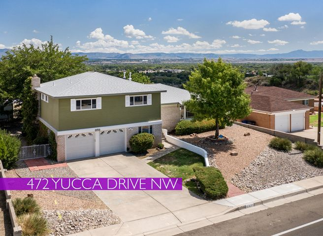 Incredible views from this desirable, large bluff lot. This home has two large living areas, a large kitchen with views from the kitchen sink and a formal dining room. The large family room has a fireplace, a wet-bar and sliding glass doors that look out on the amazing view and open to a covered patio. Great for entertaining. Plus, there's a convenient 1/2 bath downstairs too. The good-sized Master bedroom has a walk-in closet and a 3/4 bath. Three more bedrooms upstairs with a full bath. Full-sized separate Laundry Room on main level and an attached 2-door, 2-car garage. Save on your power bills with the Active Solar system. Drive in RV access. Walk to Hurley Park with trails, views and playgrounds. Easy access to I-40 for commuting and to Coors Blvd. shopping, dining and services.