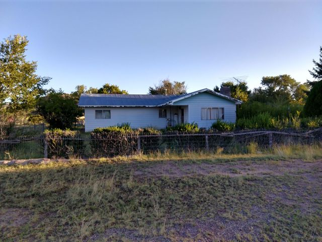This site build  home is located in the center of Datil, NM. The house dates back to the early seventies. There is a roomy kitchen, a small mudroom, a small room off the kitchen that could be made into a pantry, a large living room with fireplace,  dining room, 2 nice size bedrooms. And a full bathroom.  In addition, there is a 1959 mobile home on the property, which could be used for storage or workshop.The property is fenced. The property was on a cesspool which is no longer operational, and the house will have to get a new septic system.  There is a private well, electricity is working. The  house is sold as is