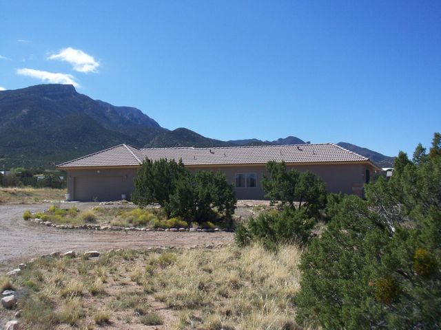 WONDERFULLY PRIVATE! AND REALLY CONVENIENT! FOUR BEDROOM WITH DRAMATIC VIEWS!!!  $440,000.  Easy access off Highway 165 takes you up to this unique, (nearly) new home on a 3 acre hill! 2,453 sq ft with unobstructed views of the Sandias + excellent views to the west of Cabezon! Comfortable home designed to take advantage of great views, as well as having tons of wall space to display artwork! Private interior courtyard is completely enclosed! Country kitchen with breakfast nook, huge living room & dining room with vaulted ceilings and picture windows! Refrigerated air! 4th bedroom makes great office. 2 & 1/2 baths. Oversize 2 car garage. Low maintenance tile roof! Over 3 acres! Room for horses, guest house, studio... No HOA. Adjacent 4 acres to the west is available for additional $70,000.