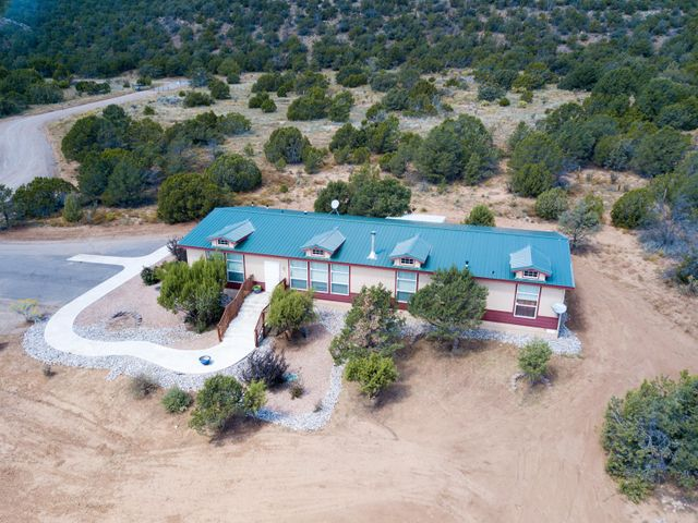 Remarkable opportunity to own 18 acres with a custom Karsten Home built locally in Albuquerque. Enjoy this open light and bright home with 5 bedrooms and 4 full baths. Perfect for larger families or in-laws. Enjoy stunning views and privacy galore. Property has electric gate to add to your privacy. Outdoor patio and walk down to a common area with fire pit and sitting area. This home is a must see.