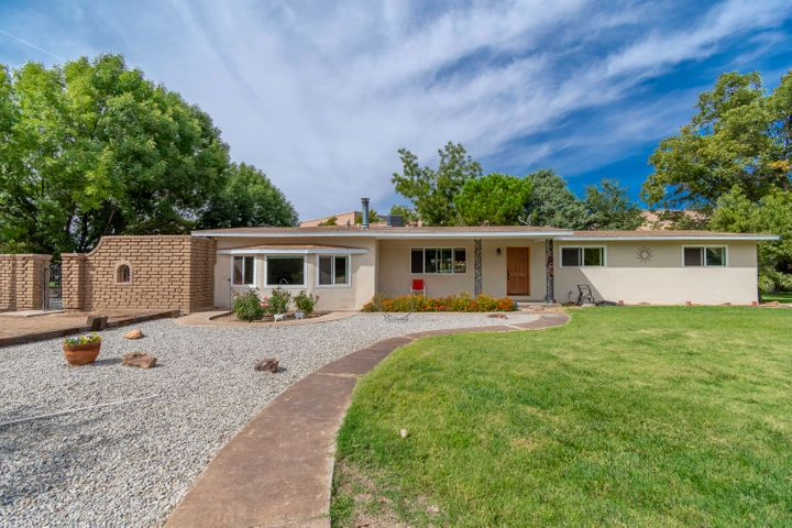 Beautifully remodeled North Valley ranch on a large 1.24 acre property filled with lush grass, cottonwoods, fruit trees and private access to the Acequia trails. Home features 3,115sf with 3 bedrooms, 2 bathrooms, 2 living areas, a sunroom and casita! New stucco, Pella windows, insulation, electric gate, 8'' piping access to irrigation water and  more. Brand new kitchen with ceiling height cabinets, granite countertops, new black stainless steel appliances and a custom subway tile backsplash.  Spacious living area with bay windows. Master suite with new flooring and a private master bath. Bath hosts dual sinks, a large soaker tub and a separate walk-in shower.  Horses welcome!  Mountain Views & Convenient Location!