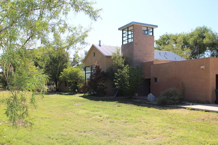 Do not miss this amazing North Valley property.  This home is a contemporary style home by Jon Anderson and has been featured in magazines.  The 1.41-acre property is set between the Rio Grande river and road with a rural secluded feel while being in the city. Walk across the threshold to find storage for your shoes and slide on your slippers.  Large windows spread natural light across the expanse of the great room.  Need a buffer from the rest of the house, you can have a dining area or home office with a half wall looking out the windows into a scenic planter.The kitchen has more granite counter space than you will use but you will certainly love the built in cookbook shelves, storage cabinets and Viking cooktop and Subzero fridge.  The matching granite kitchen table with built in se