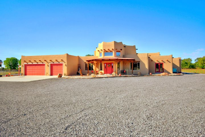 Enjoy this custom 4/5 bedroom pueblo style home on 2.6 acres. Enter your new home through a circular foyer to high ceilings, kiva fireplace, open floor plan and a custom kitchen with island. This home begs for entertaining inside and out. Tons of windows bring in natural light and lets you enjoy the views of your beautiful backyard, patios and swimming pool. Oversized Master has extra sitting area, separate patio and huge closet. Master bath has separate walk in shower and jetted tub. Three large bedrooms surround a second family room, two share Jack and Jill bath. Front office/study could be used for 5th bedroom or work out room. Behind home is fully fenced pasture area and fully fenced riding arena with covered stalls and storage area. Children will enjoy the playground with rubber bark.