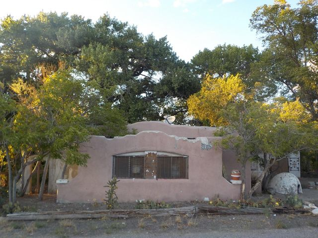 This charming adobe home was a trading post back in the 1800s!  Lovely mature trees grace the embankments of the active acequia.  The interior of the home has southwestern appeal.  A sturdy basement can be used for extra storage.  The casita next door is included, and is allowed by the special Algodones zoning, along with light retail and commercial.  Seller credit for utility allowance at closing.  The vacant block building is awaiting your creative design.  The lot extends past the footbridge over the seasonal water.  Algodones is a wonderful small town with easy commuting to Santa Fe, Rio Rancho & Albuquerque.  Come see this unique property!