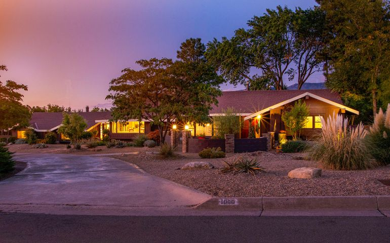 This custom Mid-Century Modern masterfully preserves all of its architectural design while seamlessly incorporating 21st century flare. A true Four Hills gem situated on large parcel with views of the Sandias. A gated parking area with large storage outbuilding. Offering a versatile floor plan, the home features 3 bedrooms, 3 bathrooms, 3 large living areas, a gorgeous kitchen, formal dining room, and an eye-catching wet bar. Like to have guests? This home effortlessly integrates inside and outside entertaining via the oasis of a backyard that features a fire pit w/ hand painted reclaimed lumbar stools, manicured lawn, covered patio, a tree house, and a serene pergola. Both professionally landscaped and interiorly designed it shows like a home in HGTV magazine. With perfectly placed design