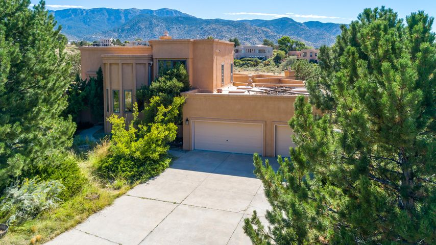 Spectacular views from inside and out of this stunning, updated Sandia Heights home on 3/4 acres!  So many updates over the last few years...over $60,000 in BAC single ply 50 mil membrane roof, skylights and owned solar PV modules. Not to mention the porcelain tile flooring, granite counters, updated kitchen appliances and more! Open area/arroyo behind affords opportunities to view wildlife and easy access to Elena Gallegos and the foothills. Welcoming floor plan with abundant natural light, you'll enjoy entertaining or everyday living in the family/kitchen/breakfast nook that draws you out to the wrap-around deck with views in every direction. Private master suite upstairs, plus 3 downstairs bedrooms with en-suite baths and oversized 3 car garage...this is the one you've been waiting for!