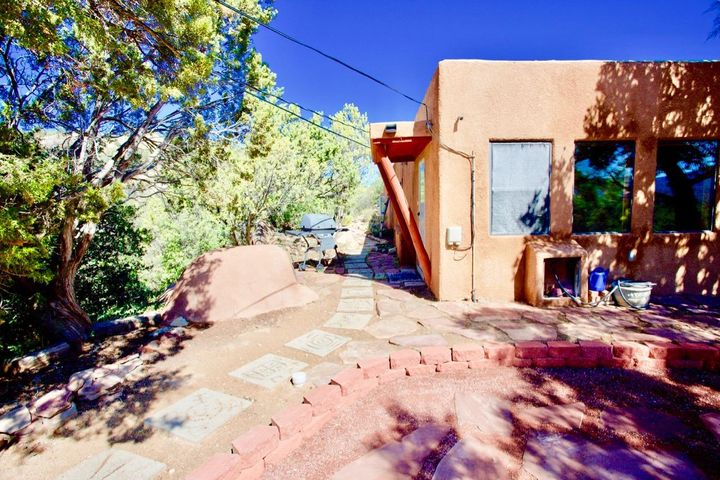 Amazingly UNIQUE pueblo style home located on 1.45 acres with incredible mountain views! It has a gated driveway, a beautifully updated kitchen with quartz countertops, 2 living areas, spacious bedrooms, 4 fireplaces, and more mountain charm than you can imagine! Enjoy Santa Fe style without Santa Fe prices. Just an 11 minute drive from Albuquerque, this mountain retreat has a very rural, peaceful feel. Includes a large screened-in patio, an outdoor courtyard, a private well and 3,000 gallon storage tank, a brand NEW septic system, newer roof and stucco, detached 2 car garage with storage, an additional shed, and great, natural landscaping. Beautifully updated home with over $59K of improvements over the last year. It's move-in ready with inspections and repairs already done!