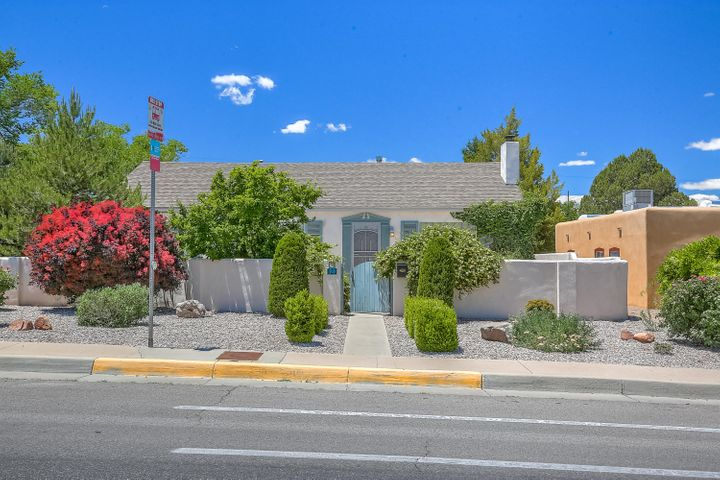Motivated Seller! Solid stucco wall surrounds this huge corner lot with unobstructed views of the Sandias. Pitched roof with attic, original enormous casement windows, porcelain countertop in kitchen, updated Italian tile flooring in sunroom, upgraded electrical to 200 amps and insulated two car detached garage. The backyard features beautiful lawn and large patio surrounded by evergreen shrubs and fruit trees - it is perfect for entertaining! Close to restaurants, hospitals, the airport and parks. Take a moment to stop and smell the roses at this incredible home!