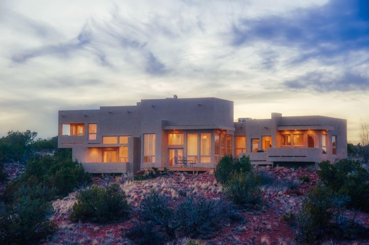 SPECTACULAR ENDLESS, JAW DROPPING 360 FOREVER VIEWS TO THE ORTIZ MTS AND BEYOND. GLASS WALLED, CUSTOM, ARCHITECT DESIGNED SITE SPECIFIC OPEN FLOOR PLAN CONTEMPORARY SANCTUARY NOW LISTED BELOW APPRAISAL. PREPARE MEALS IN THE GOURMET KITCHEN ON A ONE OF A KIND TRANSLUCENT BACKLIT QUARTZITE ISLAND FEATURING WOLF, SUBZERO, AND BOSCH APPLIANCES AND A GLASS WALL IN THE DINING ROOM FOR MORE EXTRAORDINARY VISTAS. TWO STORY GREAT ROOM WITH  FLOOR TO CEILING WINDOWS ON THREE WALLS OFFERING VIEWS TO THE ORTIZ MTS. AND MONTEZUMA CREST. UNPARALLELED SUNSET VIEWS AND BIG SKY DAYS AND STARLIT NIGHTS.EXPANSIVE 2 STORY MBR. 2ND EN SUITE MBR. GUEST HOUSE, BALCONYS FROM ALLROOMS. RADIANT HEAT AND REFRIGERATED AIR IN RESIDENCE AND GUET HOUSE. A TRULY INCOMPARABLE PROPERTY IN A PRIVATE SETTING.