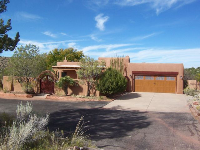 LOOKING FOR A SMALLER, MORE AFFORDABLE, CUSTOM HOME ON ACREAGE? THIS IS IT!  $355,000 for this convenient 1,776 sq ft, 2 bedroom + office on over 3 ACRES! Beautiful, reasonably sized home with two of the most beautiful & inviting courtyards in Placitas! Stunning Sandia mountain views as well as views to the north! Great floor plan with little wasted space! Beautiful kitchen with great custom cabinets, new smooth cook top and double (convection & microwave) ovens. 2 bedrooms with huge master suite that includes bedroom, sitting room & office! Tons of covered patios to enjoy views all around! Oversize 2 car garage. 24' x 14' detached workshop too! 3 acre tract allows horses & could even be easily divided into 2 parcels. No HOA; no HOA fees! New stucco! On paved road with easy access to I-25.