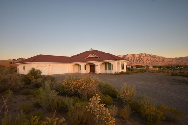 A FABULOUS custom home on 8/10 acre with the best views in Rio Rancho. This magnificent home has three master bedroom suites, each with their own private bathroom, two Jacuzzi tubs, a bonus bedroom and guest bathroom, beautiful gourmet kitchen with plenty of countertop space, built-in stove & microwave, island w/ cooktop & pantry, large dining room, extra-large living room with raised ceilings, wet bar and fireplace, breathtaking views of Sandias and Manzanos from kitchen, LR, Sunroom and backyard, oversized three car garage with bonus storage space and additional parking in the driveway. Well water (no water bill), double purification system and instant hot water.
