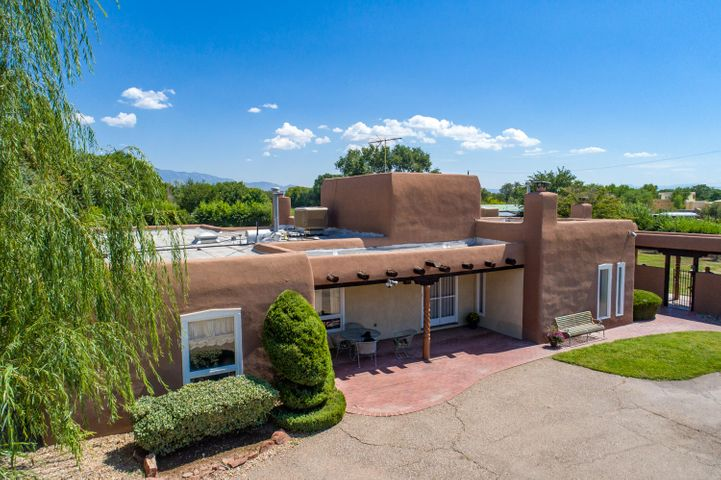 Rare 2.25 acre property in the Near North Valley.  Custom adobe home with brick floors, kivas fireplaces and wood ceilings.  Built in 1984 this home was crafted with such care from the custom arched doors, gallery like hallways to the interior adobe walls.  The home sits nestled in at the end of the road in a peaceful rural setting - yet it is only minutes from Rio Grande, I-40 and I-25.  The acreage allows for horses with a small barn and working hot walker.  Beautiful outdoor living space with covered patio, swimming pool, hot tub, and fireplace.  Brick floors throughout the main living areas including the formal living room, formal dining room, family room and breakfast area.  An office complete with kiva fireplace can be accessed from the master bedroom or the hall. And a 3 car garage!