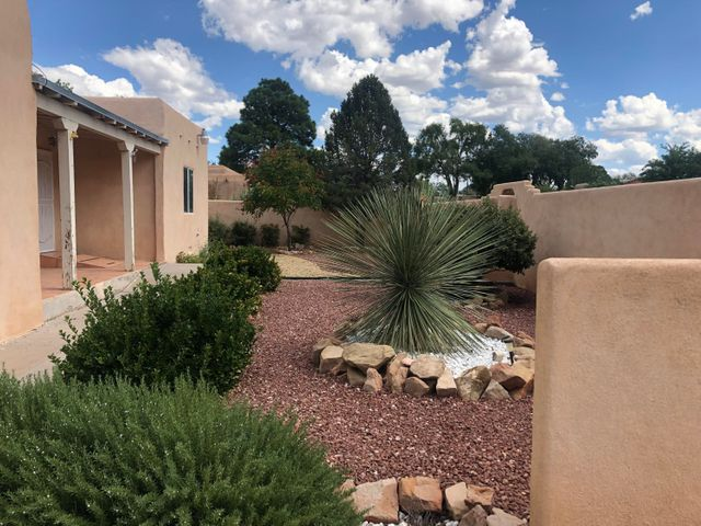 The owners have put a lot of TLC into their home! Come view this property to appreciate it! Newly refinished kitchen countertops, beautiful hardwood floors throughout, double pane windows, plus it has been freshly painted. Owner invested in an energy efficient Rheem refrigerated AC & Heating unit. The backyard is a paradise with beautiful landscaping, a fully lit gazebo offering plenty of space for outdoor entertaining with a partial view of the Sandia Mountains. Outdoor area offers a privacy wall & an attractive well built shed. Backyard has vehicle access with garage doors on both north & south ends of garage. Pride of ownership is obvious!