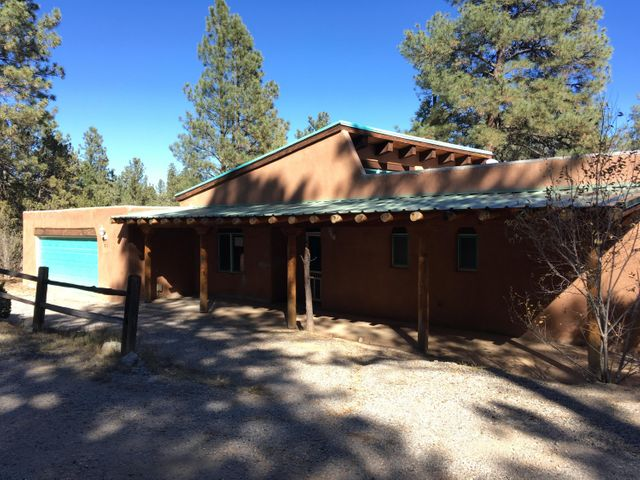 Relax among the pine trees on the wrap around deck. This  partial adobe home has 2 fireplaces and sunken living room. The guest house has 2 bedrooms and a bath. Guest house is upstairs above the workshop and boasts 1040 sqft not included in the total sqft.