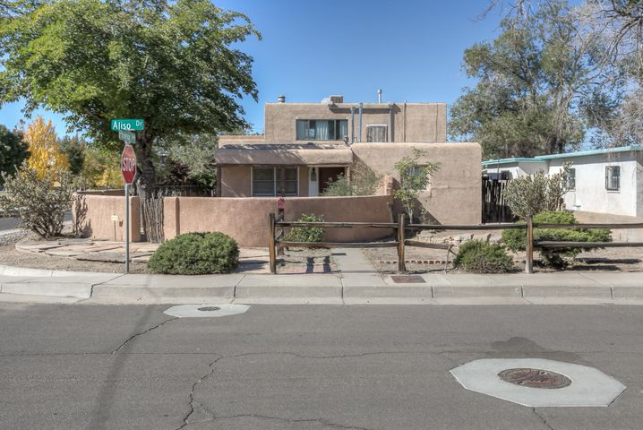 This remarkable 2 story home is located on a corner lot just across the street from a park. The home boasts brick floors, a walled courtyard, wet bar, bright breakfast nook, huge upstairs master suite with private balcony. The kitchen is with with butcher block counters and china cabinet, security system, powder room, latilla accents and backyard access. There is more than enough space on the side of the one for multiple cars, RV access or even a garage.