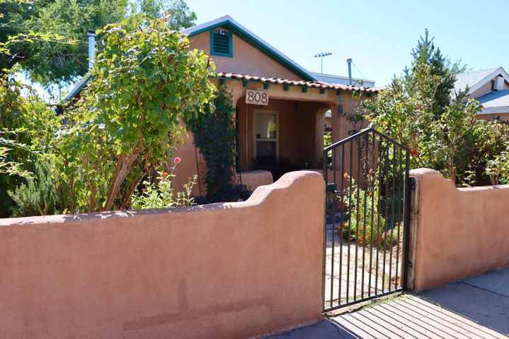 Gorgeous Shotgun Adobe located in the heart of ABQ, w/ quick access to all the best that the city has to offer. From the conveniences at your doorstep to the Traditional New Mexican beauty, this home is sure to capture your heart. Imagine sipping morning coffee on your patio while hearing a lion's roar or cozy up to a crackling fire, deep within the thick walls of this charming adobe. Glistening wood and hand made Saltillo tile floors guide your way. Period details throughout, clawfoot tubs, skeleton key locks, exposed wood beams. Updated windows, metal roof, newer appliances in Main home (oct 2019) security camera system, water heaters (2018), water filtration (2017).Back casita offers endless possibilities. Parking in rear with alley access. Come see this well maintained beauty!