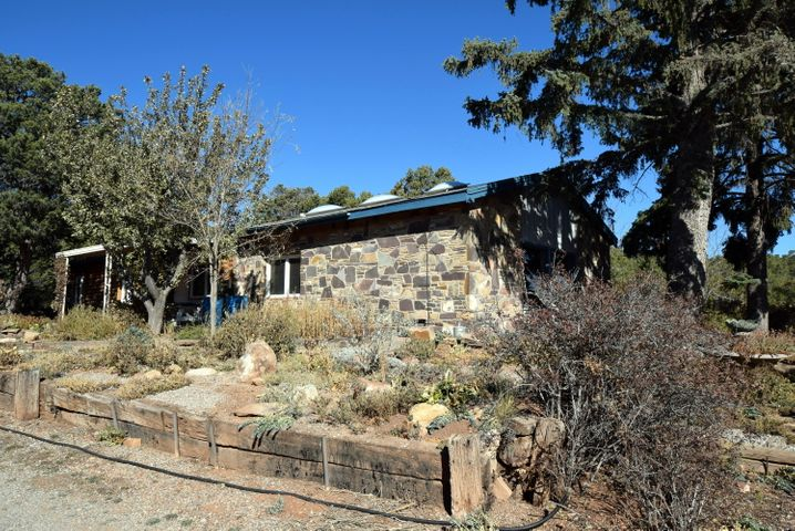 .Currently a Short Sale. Diamond in the Rough! Charm & Character With Endless Possibilities! Two Homes, One Price! Situated on 4 acres with Ponderosa's, Mature Pinon's, Fruit Trees, Pond and Terraced Gardens! Main Home needs TLC, 2 woodburning RP's 3 Bdrm, 2 Bath, Kitchen with newer appliances and granite counters. Original Home was Log, addition is Rock! Casita is two-story, 2 bedroom, 1 bath, FP and hardwood floors.