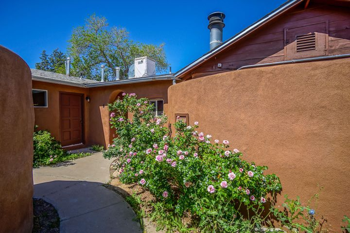 Come check out this Beautiful Adobe Style Home today! Located in a quaint 8 home gated community built to resemble a Spanish village. Private retreat in the heart of the city. Newly remodeled granite and stainless kitchen that opens to gorgeous private courtyard. Refinished brick floors. Artistic Mexican tiled baths. Wood beamed ceilings in the living area with skylights and wood burning fireplace. Custom carved woodwork and stained glass. Energy efficient low E windows. Updated Lighting. Seconds away from Old Town, Museums, Restaurants, Shopping, Parks, Bosque Trails just moments away! Come Check out your new home before it's someone else's!