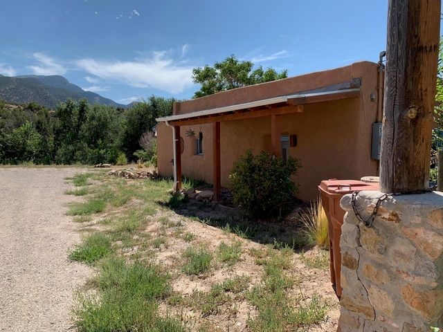 WONDERFUL COZY ADOBE IN THE VILLAGE OF PLACITAS! $150,000. Majestic Sandia views from this historic adobe property! Seller was told the home is over 100 years old! 773 sq ft with awesome adobe walls with exposed beams (vigas) & wood ceilings throughout! Brick floors, 9' tall ceilings & new vinyl windows. The 3/4 acre lot includes 2 acequias (irrigation ditches) at both the front & back of the property, so on wet years you can hear the sweet sound of running water! The land goes back though the beautiful arroyo to the south! The home could easily be made into 2 bedrooms; there is room to add on! Updated septic was installed in 2009 which allows for up to 3 bdrms. Probably built in the late 1800s! There is a lot of history here! Could make a great little Air B&B property. No restrictions.