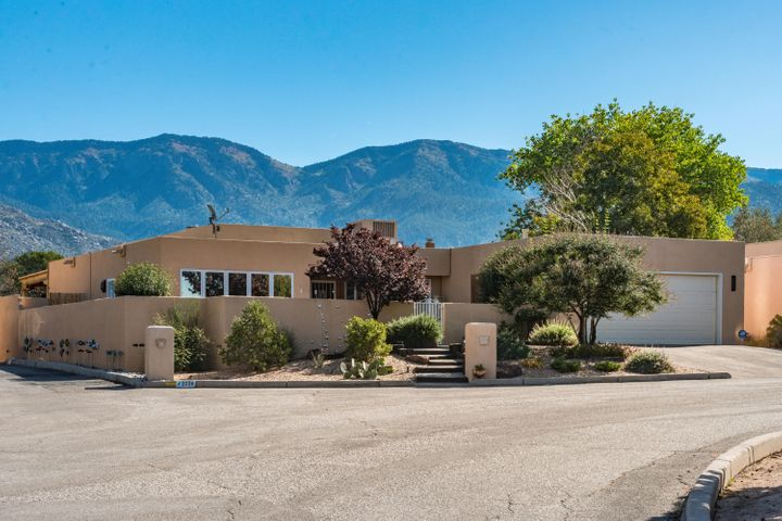 Stunning views of the Sandia mountains and the City lights! Exceptional outdoor living features with this single-level home include private, heated newly refurbished gunite pool and spa, SW covered patio cook station, new upg landscape with lighting and expanded pool deck and heated sunroom w/ Kiva fireplace. Beautiful front courtyd overlooks city lights. New hardwood, interior trim, paint and lighting with designer touches. Raised beam ceiling in LR w/ gas log fireplace, breakfast area off kitchen, formal dining room, spacious bedrooms with ample closets. Radiant & HVAC systems w/ refrigerated air. Easy access to Tramway, Paseo, trails and open space!