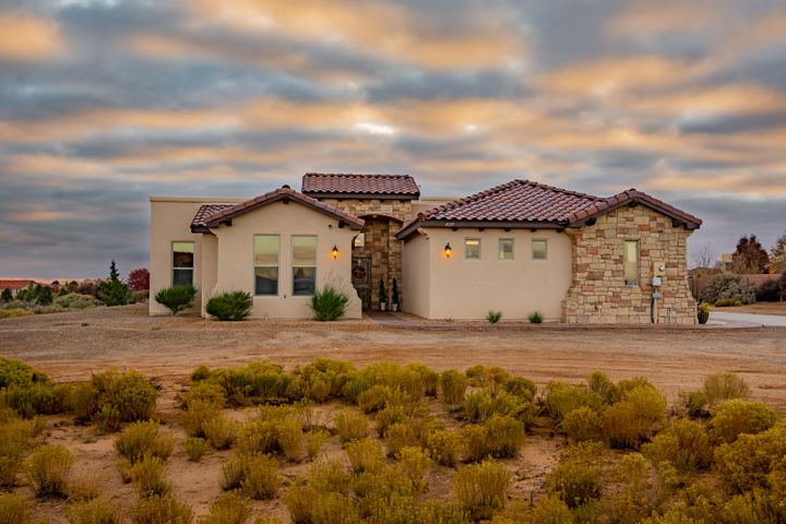 Stunning custom built beauty by Prestigious Homes located in the heart of Rio Rancho on a 1.07 acre property. Home features 2,797sf w/ 4 bedrooms, 3 full baths, a home theater and 3 car garage.  Beautiful living area with travertine floors, raised ceilings with wood beam accents, a pellet stove and built-in media center with surround sound. Chefs kitchen w/ designer cabinetry, granite countertops, built-in double oven/microwave, custom range hood, cooktop, prep island, pantry, high top bar with seating and breakfast nook. Catch the latest movie in your home theater with wet bar! Mater suite with private bath. Bath host his/hers vanities w/ vessel sinks, jetted tub, walk-in shower w/ dual heads and a walk-in closet. Great outdoor space with a built-in grill & bar, playground & amazing views