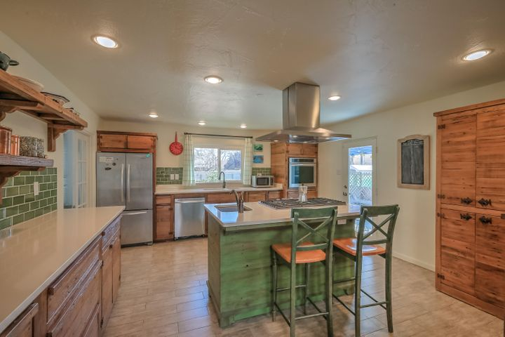 This immaculate home in the UNM area boasts upgrades galore! The interior is flooded with natural light thanks to large windows and skylights. The kitchen looks like it came right from the pages of your favorite home magazine, with beautiful custom cabinetry, stainless steel appliances and a gas stove and sink in the island. The master bath is a breath of fresh air with subway tiles and frosted window. A large yard and covered patio will keep you outdoors all year. Make this your home today!