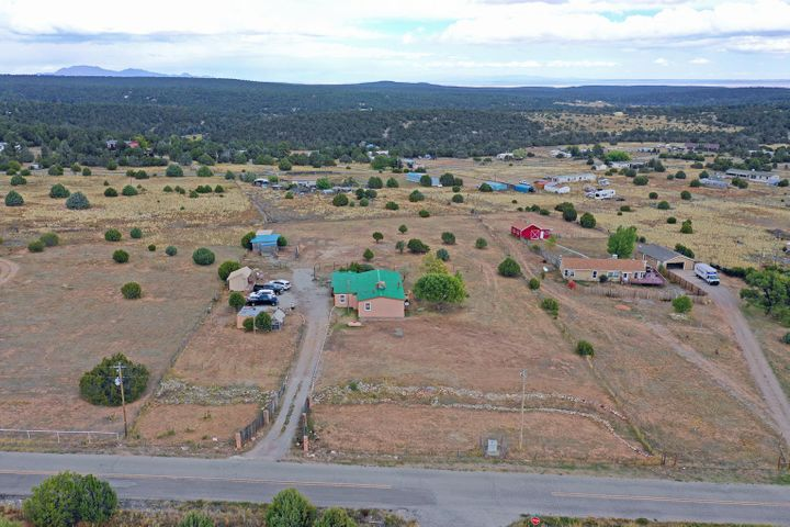 Located in the rolling hills adjacent to the Cibola National Forest, this 3 bed 2 bath home reflects the charm of rural living just outside Albuquerque. Set on a brand new foundation system, and a newly installed septic system, this house sits in the middle of a level 2 acres. There are two storage sheds, a small green house and covered  stalls used to house animals - chickens, pigs as well as horses. Along with a large gravel parking area and a sizable covered porch, the house has been well maintained and trimmed. From the porch there is an entry mud room that opens up into a central living, kitchen and dining area. The communal area is equally flanked by the bedrooms and bathrooms. The entire property has been maintained with care and welcomes new owners graciously.