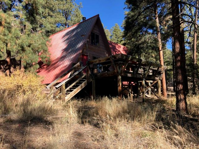 Tucked away near the top of Area 3 lies this charming A-frame home on over half an acre. Enjoy a wood-heated living room with access to the large front deck on the East side that boasts amazing views of the serene Jemez Mountains. A true cabin feel throughout this home with more than ample storage, multiple spacious closets, large master with full master bath,  and TWO lofts. Exterior features a detached two car garage w/ storage racks and separate storage shed. Bang for your buck and ready for someone to make it ''home!''