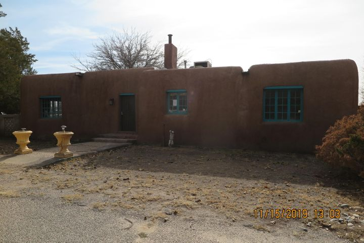 Pueblo style home on 1 acre parcel. Large livingroom with Beam ceilings, hardwood floors and fp. Formal dining room, 1.75 baths (freestanding  antique tub), separate utility room, enclosed porch, 3 large bedrooms one with sitting room. Detached workshop/storage. Privacy  Block wall.