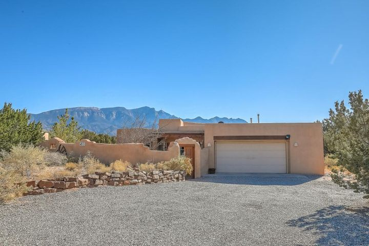 Walk through your front door into a great room with Sandia mtn views, a 12 ft high beamed ceiling, wood floors & a plastered kiva fire place. Sun-filled & open great room/kitchen/dining areas. Mstr suite opposite other bdrms w/ separate tub, shower, dble vanity & walk-in closet. Den could be a 4th bdrm. New heating & central air installed in 2017 & many newer appliances. Private, beautifully-landscaped front courtyard w/pond for outdoor living on a .75 acre view lot. Over-sized 2.5 car garage, electric-ready 18x11 out building perfect for office or studio. Close to I-25, restaurants, & outdoor recreation in the mountains.