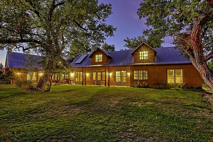 Fabulous Northern NM Adobe custom home with a passive solar design! So much attention to details and extra special touches in this gorgeous home! Beautiful Hand Hew Oak Beams! Awesome kitchen with lots of work space, granite countertops, custom cabinetry, high end appliances;  Subzero, Bosch and Wolf range.  Gorgeous oak wide plank wood  and acid etched concrete flooring.  Variance plaster walls, huge loft area, w/powder bath, great for family room or fourth bedroom. Green/Eco materials, beautiful custom La Puerta  and Marvin Wood windows and doors. European tile in kitchen and baths. Slate, glass and tumbled marble tile in master bath.  European style closets in bedrooms.  Situated in   mature cottonwood trees along in the Bosque Greenbelt, Bosque access!  Peaceful Eastside neighborhood!